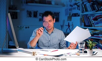 Tired businessman sits at a table, holds documents and a magnifying glass.