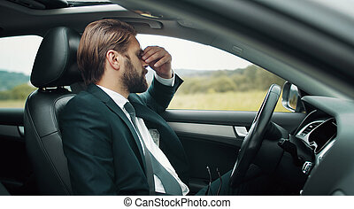 Tired businessman sitting driver's seat