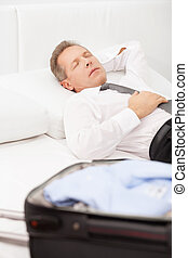 Tired businessman sleeping. Tired grey hair man in shirt and tie lying on bed and keeping eyes closed while luggage laying on bed