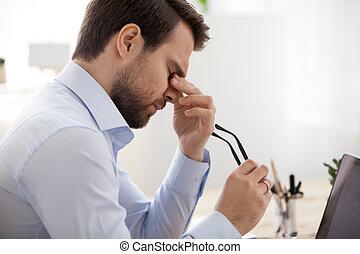 Tired businessman taking off glasses feeling pain eyestrain headache