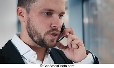 Tired businessman talking on a cell phone