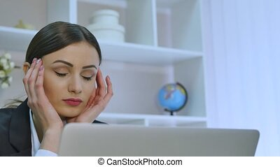 Tired businesswoman having a headache while working on her laptop in bright office