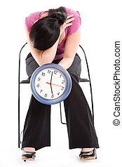 Tired businesswoman holding a clock - A tired businesswoman...