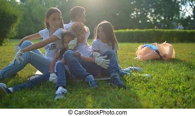 Tired but cheerful volunteers sitting on grass together -...