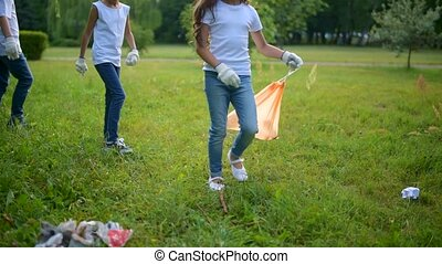 Tired but mindful little volunteers competing in cleaning -...