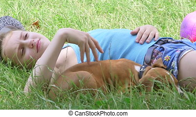 Tired child with puppy relaxing on grass in summer garden