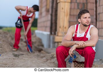 Tired construction worker resting