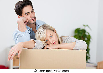 Tired Couple Leaning On Cardboard Box - Mid adult tired...