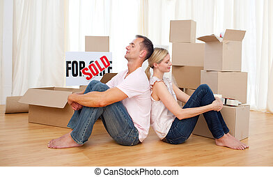 Tired couple relaxing sitting on the floor