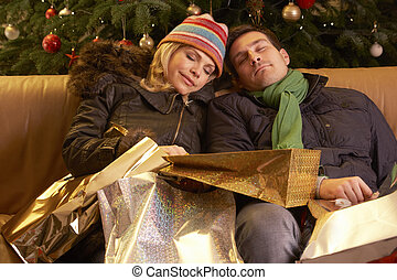 Tired Couple Returning After Christmas Shopping Trip