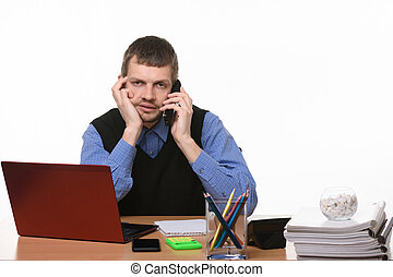 tired employee talking on the phone in an office setting