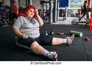 Tired fat woman sits on the floor in gym