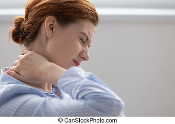 Tired fatigued business woman office worker feeling pain chronic discomfort injury hurt rubbing stiff tensed sore neck muscles suffer from fibromyalgia ache after sedentary work in incorrect posture.