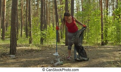 Tired female activist collecting garbage outdoors - Tired ...