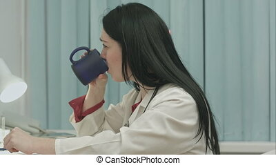 Tired female doctor sits in a medical office in the clinic and writes diagnose of patient