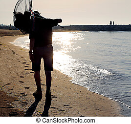 tired fisherman with nets walks by the sea