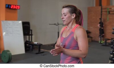 Tired fitness woman walking in gym