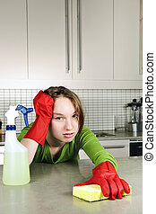 Tired girl cleaning kitchen