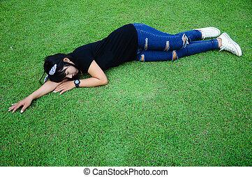Tired Girl Sleep on grass in the Garden