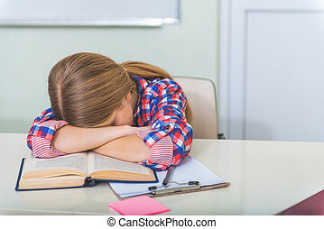 Tired girl sleeping in classroom