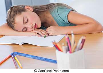 Tired girl sleeping on her homework