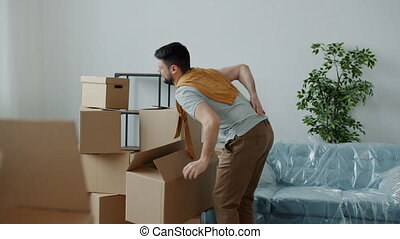 Tired guy is bringing home heavy boxes then touching back suffering from backache during relocation to new apartment. Health problems and people concept.