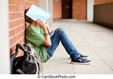 tired high school student using book cover his face