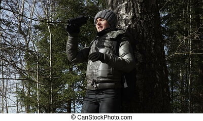 Tired hiker woman with binoculars near tree