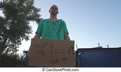 Tired hobo man on the street. Sign on cardboard - will work ...