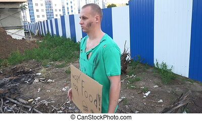 Tired hobo man on the street. Sign on cardboard - will work for food
