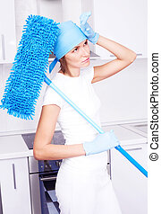 tired housewife - tired young housewife with a mop in the...