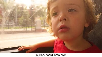 Tired little boy travelling in bus and looking through the...