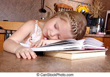 tired little girl sleep at books