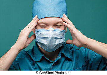tired male surgeon in mask on blue background, close up