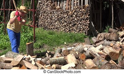 Tired man chop firewood and drink water from plastic bottle. Young worker prepare wood in summer. Static shot. 4K