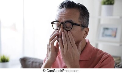 tired man in glasses rubbing eyes at home - vision, eyesight...