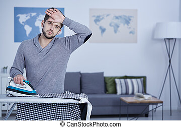 Tired man ironing