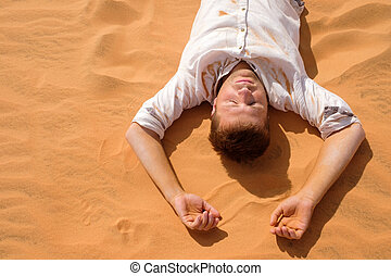 Tired man lying on the sand in a desert.