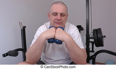 Tired man sleeping with two small dumbbells