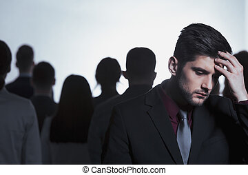 Tired man standing in crowd