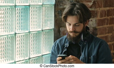 Tired Man Texts Message near Window - Tired bearded man...