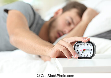 Tired man turning off alarm clock in the bed
