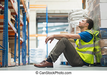 Tired manual worker sitting on floor in warehouse