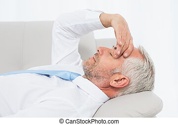Tired mature businessman resting on sofa in living room
