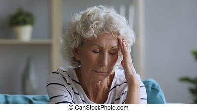 Head shot close up exhausted middle aged hoary woman massaging temples, suffering from painful feelings, migraine alone at home. Tired mature older female pensioner having headache, mental stress.
