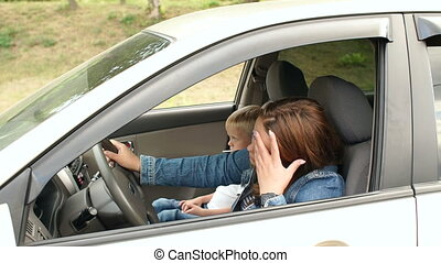 Tired mother sitting behind the wheel of a car, her little son indulges on a seat