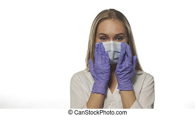 Tired nurse in robe smooths her face in mask with gloves. Blonde beautiful young woman looks at white background staring directly into camera. High quality 4k footage