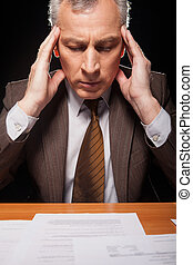 Tired of paperwork. Senior man in formalwear sitting at his working place and holding head in hands while isolated on black background