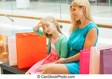Tired of shopping. Blond hair mother and daughter sitting on the bench in shopping mall while little girl keeping eyes closed and touching forehead