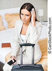 Tired of traveling. Depressed young businesswoman in formalwear holding head in hand while sitting on the bed in hotel room